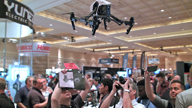Drone flying over a crowd of people who are taking photos of the drone.
