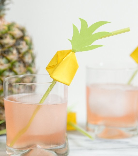 Pineapple Origami on a straw in a glass of juice. Pineapple behind