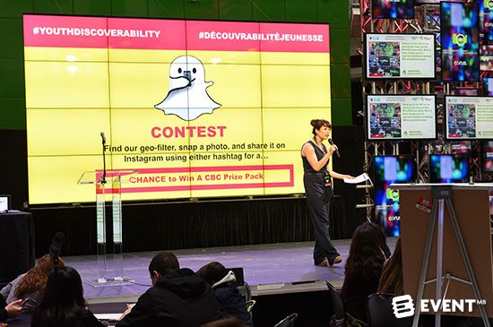 Person speaking with a screen behind her that says there is a contest for the first person to snapchat with a geofilter and hashtag on instagram or facebook gets a prize.